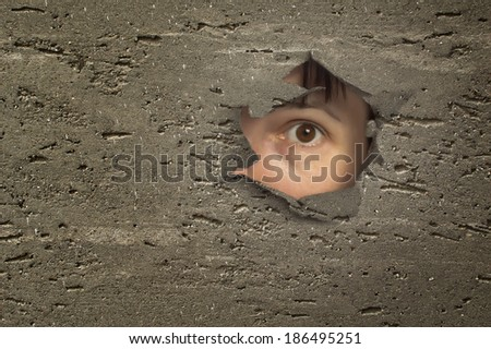 Eye looking through a hole in wall. - stock photo