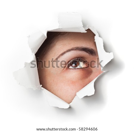Eye looking through a hole on a wall or paper - stock photo