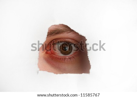 Eye looking through hole on paper surface