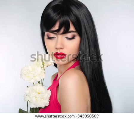 Eye makeup. Long hair. Beautiful brunette woman with luxurious smooth shiny straight hairstyle.  cosmetics, haircare. Girl with white flowers.  - stock photo