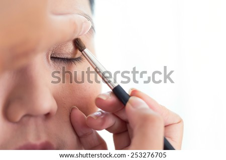 eye makeup with brush on pretty woman face