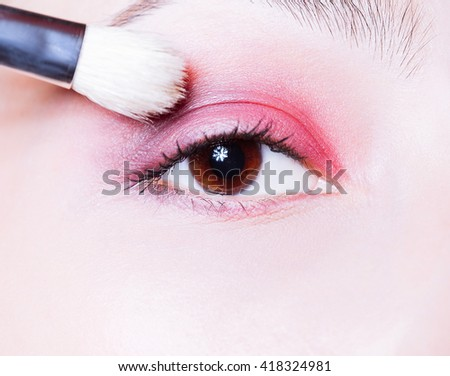 Eye makeup. Woman applying pink eyeshadow powder. Close up shot