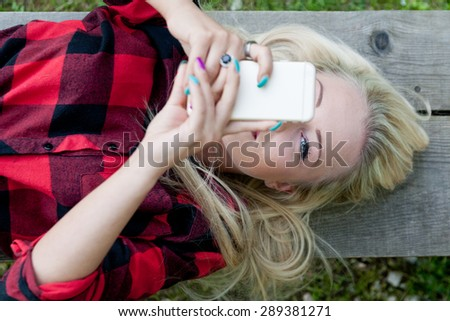 eye of a girl spotting you from behind her mobile phone because she's in control - stock photo