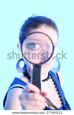 Eye of the girl in a magnifier covered by blue light - stock photo