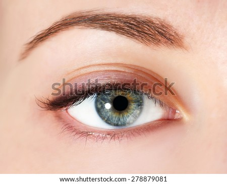Eye of young woman with tear drop close up - stock photo