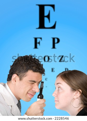 eye test - doctor and patient with the eye chart in the background - stock photo