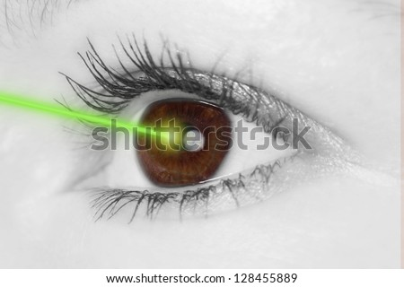 Eye with laser beam - stock photo