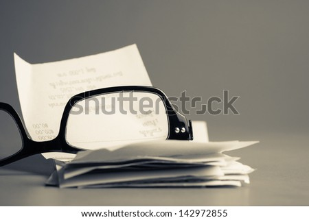 Eyeglasses and bills on gray background (home economic or financial work concept) - stock photo