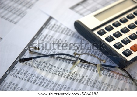 eyeglasses and calculator on the paper tables