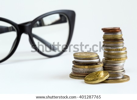 eyeglasses and coins on a white background close-up, business, finance