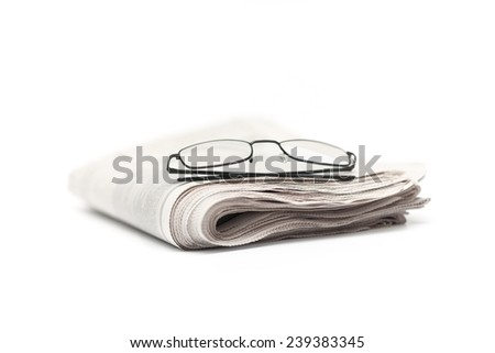 eyeglasses and newspaper on white background. - stock photo