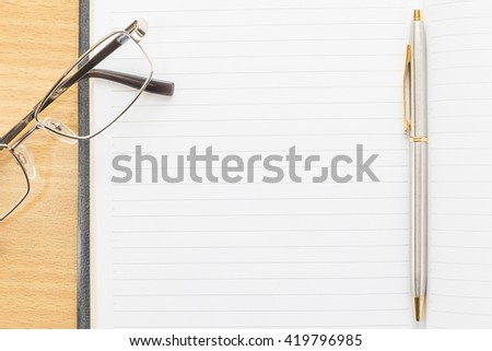 Eyeglasses and Pen on notepad with blank page on wood table - stock photo