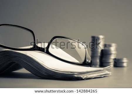 Eyeglasses and pile of bills for accountancy calculation concept - stock photo