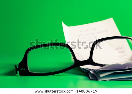 Eyeglasses and receipts on green background  (home economic or financial work concept) - stock photo