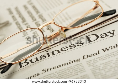 Eyeglasses lie on the newspaper with title Business day. A photo close up. Selective focus - stock photo