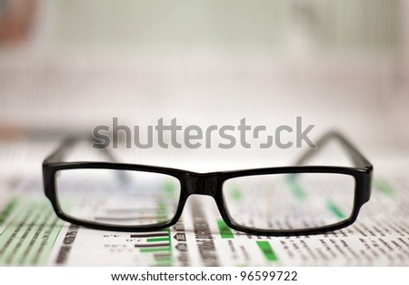 Eyeglasses lying around newspapers - stock photo