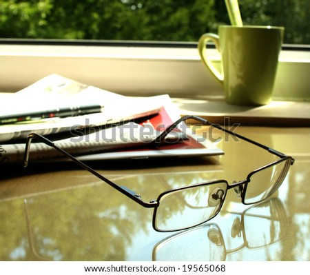 eyeglasses, newspaper on table and green cup - stock photo