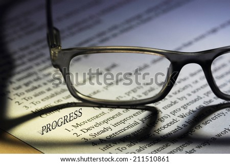 "Eyeglasses on a paper , focus on a 3D word ""Progress"" with shallow depth of field"