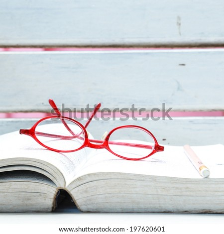 eyeglasses on book - stock photo