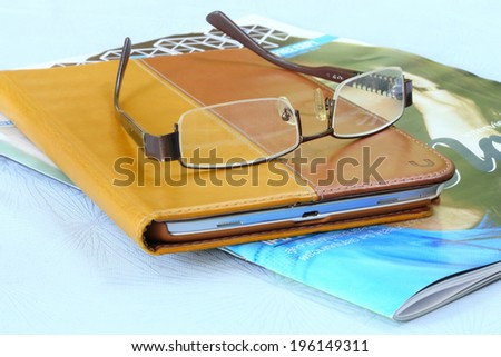 Eyeglasses on ipad and book - stock photo