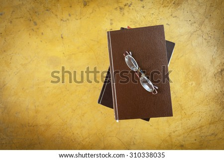 Eyeglasses on old book with vintage style background  - stock photo