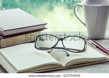 eyeglasses on open notebook with book,pen and coffee cup on rainy day window background,vintage filter - stock photo