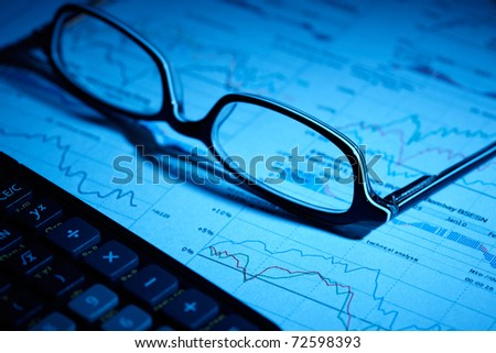 eyeglasses on paperwork with calculator in front - stock photo