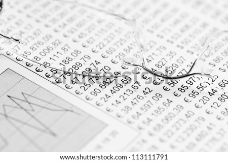 Eyeglasses on top of a sheet of paper white a chart and numbers. High contrast, shallow depth of field. - stock photo