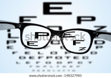 eyeglasses over a blurry eye chart - stock photo