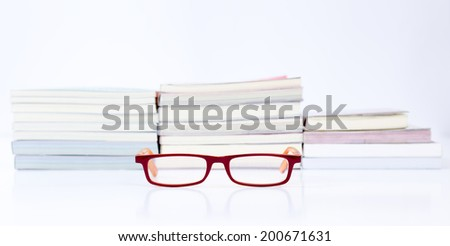 Eyeglasses with stack of book background - stock photo