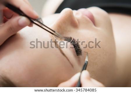 Eyelash Extension Procedure.  Woman Eye with Long Eyelashes. Lashes. Close up, selected focus. Shallow DOF. - stock photo