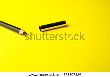 eyeliner on a yellow background - stock photo