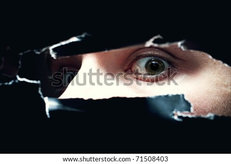 Eyes frightened young man looking out of  hole in wall - stock photo