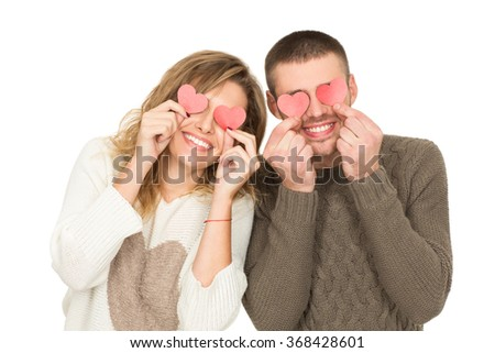 Eyes full of love. Studio shot of a cheerful young couple laughing holding little red hearts to their eyes isolated on white - stock photo