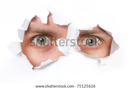 Eyes looking through a hole in a paper isolated - stock photo