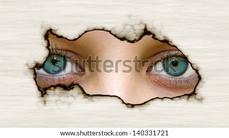 Eyes looking through a hole in paper - stock photo