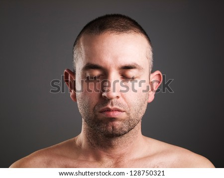 Eyes man closed isolated on dark background. He is caucasian. - stock photo