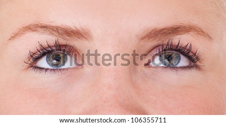 Eyes of an attractive teenage girl looking up. All on white background.