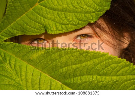 Eyes of young girl, green leaf - stock photo