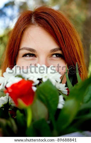 eyes of young woman with red hair and a bouquet
