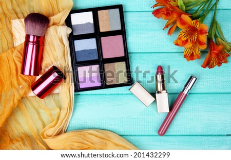 Eyeshadow, brushes, lipstick and flowers on color wooden background - stock photo
