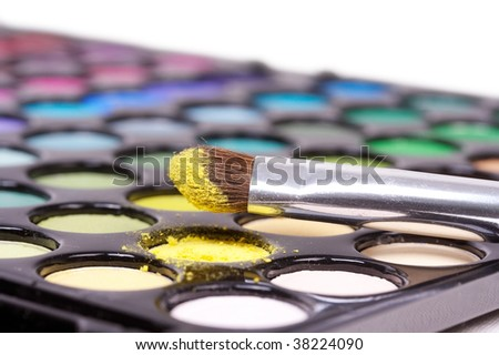 Eyeshadows with professional make-up brush on yellow pattern - stock photo