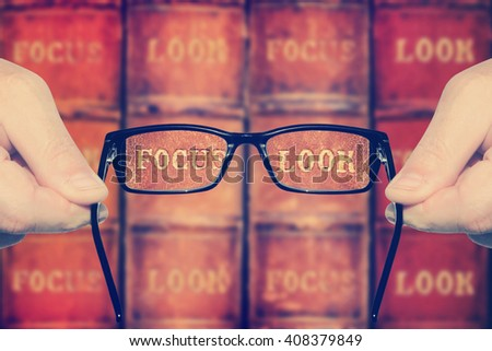 Eyesight test. Optometrist's hands holding and offering eye glasses for the acute eyesight (in focus) against the poor eyesight on the books. Concept of acute eyesight return. Toned vitage colors - stock photo