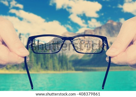Eyesight test.Optometrist's hands holding and offering eye glasses for the acute eyesight (in focus) against the poor eyesight at nature landscape .Concept of acute eyesight return.Toned vitage colors - stock photo