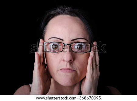 Eyesight, woman wearing strong, powerful, funny glasses. Black background with copy space. - stock photo