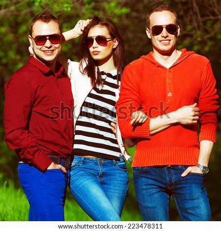 Eyewear and blue jeans concept. Portrait of fashionable friends in trendy casual clothing walking in the park together. Stylish sunglasses. Sunny autumn weather. Hipster style. Outdoor shot - stock photo