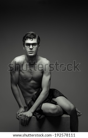 Eyewear concept. Beautiful (handsome) muscular male model with nice abs posing in trendy glasses undressed. Boy sitting on wooden cube. Vogue style. Copyspace. Black and white (monochrome) studio shot
