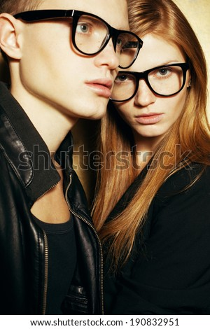 Eyewear concept. Family portrait of gorgeous blond fashion twins in black clothes wearing trendy glasses and posing over golden background together. Perfect skin. Vogue style. Close up. Studio shot - stock photo