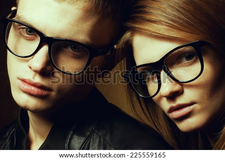 Eyewear concept. Family portrait of gorgeous blond fashion twins in black clothes wearing trendy eyeglasses posing over brown background. Perfect skin with freckles. Vogue style. Close up. Studio shot - stock photo