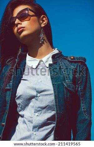 Eyewear concept. Fashion portrait of stylish brunette in trendy sunglasses and jeans jacket. Luxurious vintage earrings. Urban grunge style. Outdoor shot - stock photo